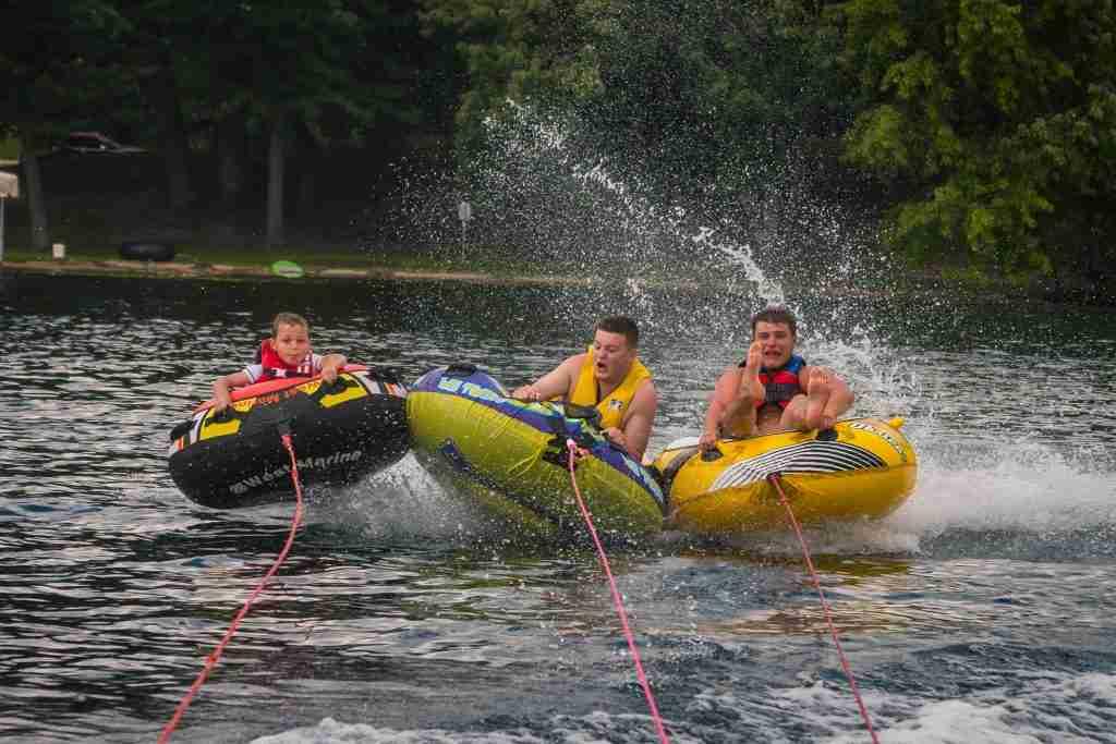 3 boys on tubes splashing behind the boat
