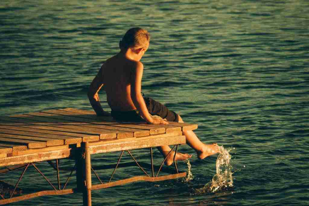 A boy sitting on the end of a dock kicking water