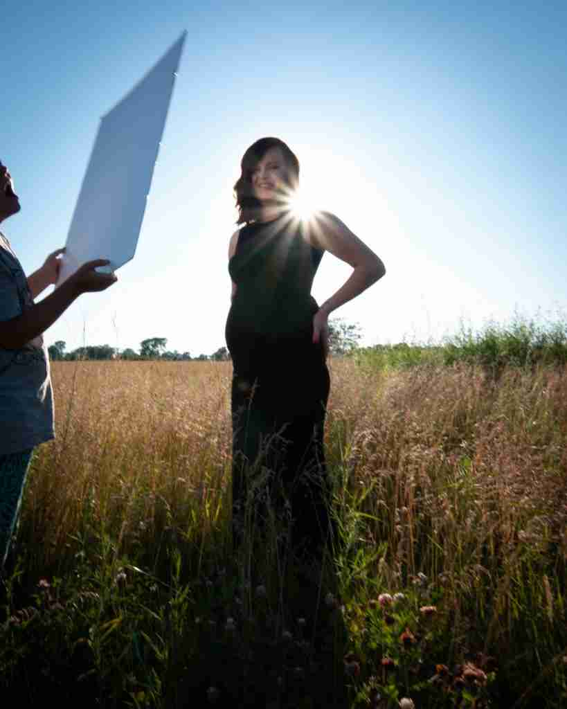 Assistant holds a tagboard used as a reflector at a photo shoot.