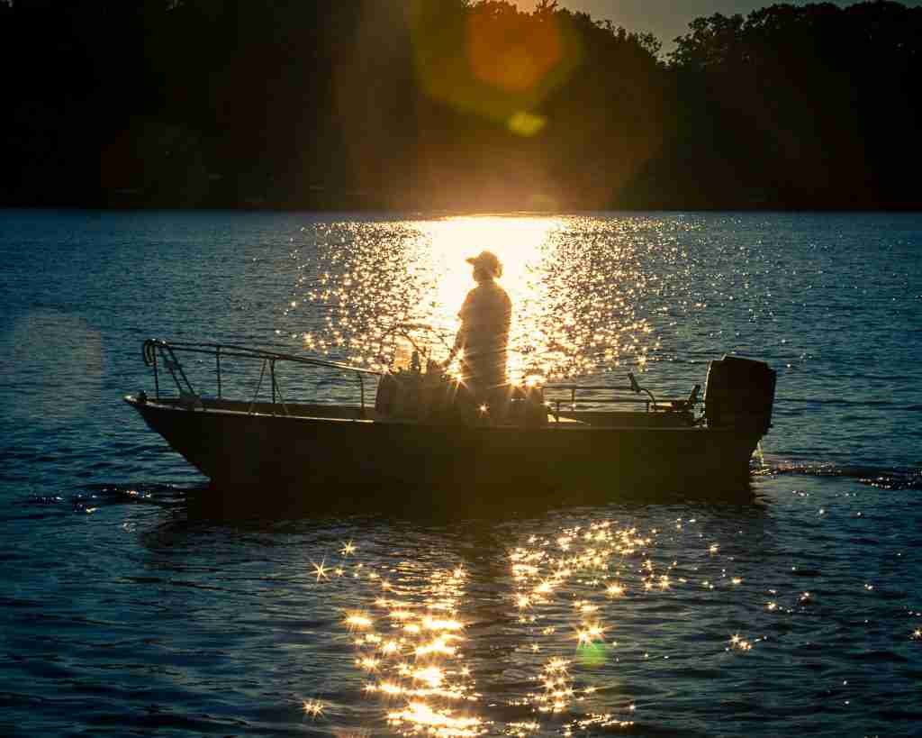 Man on a boat with starbursts on the water using aperture