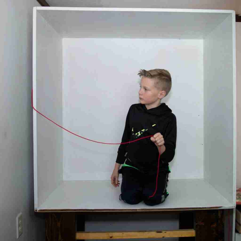 Another boy in a box holding a cord for staging