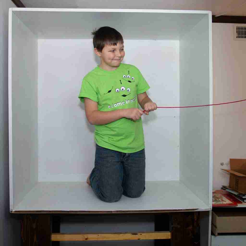 A boy in a box holding a cord for staging