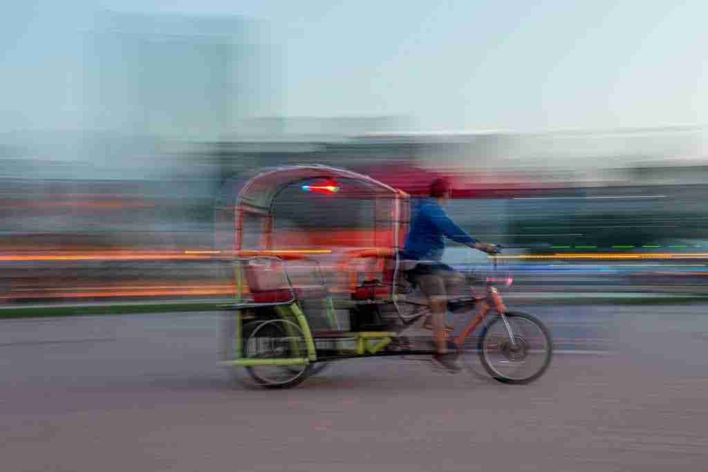 A panning shot of a Pedicab in front of the Buckingham Fountain