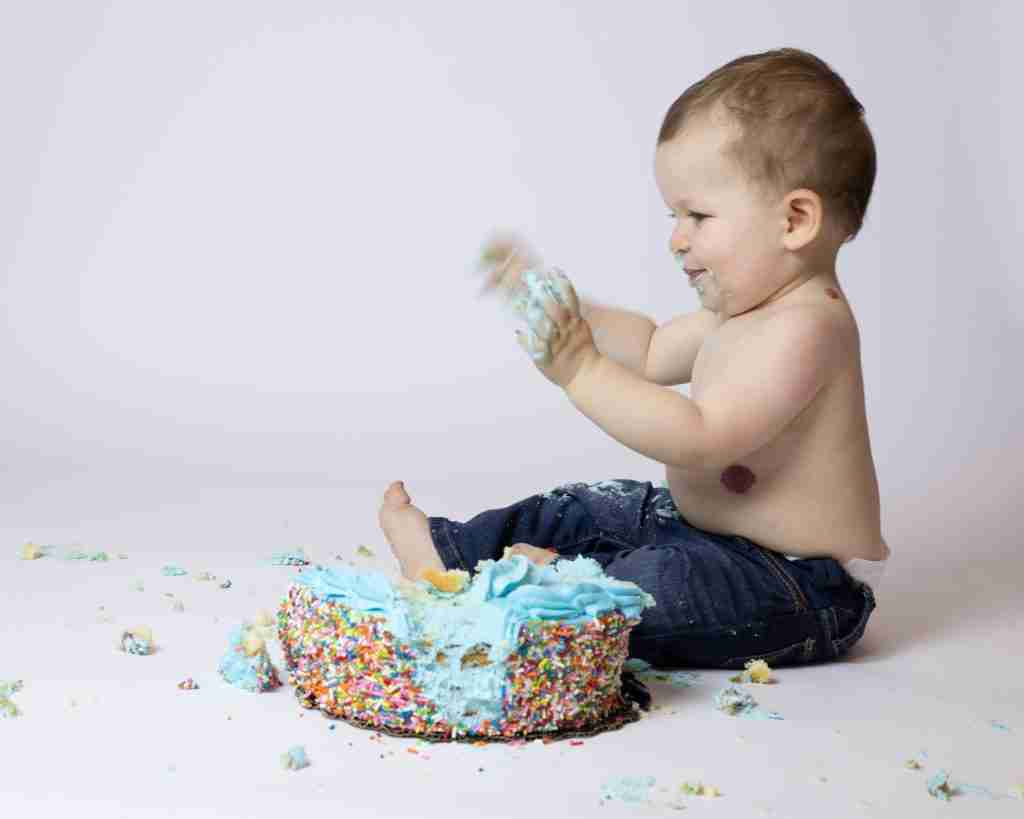 Baby with blurry hands making a mess with a birthday cake