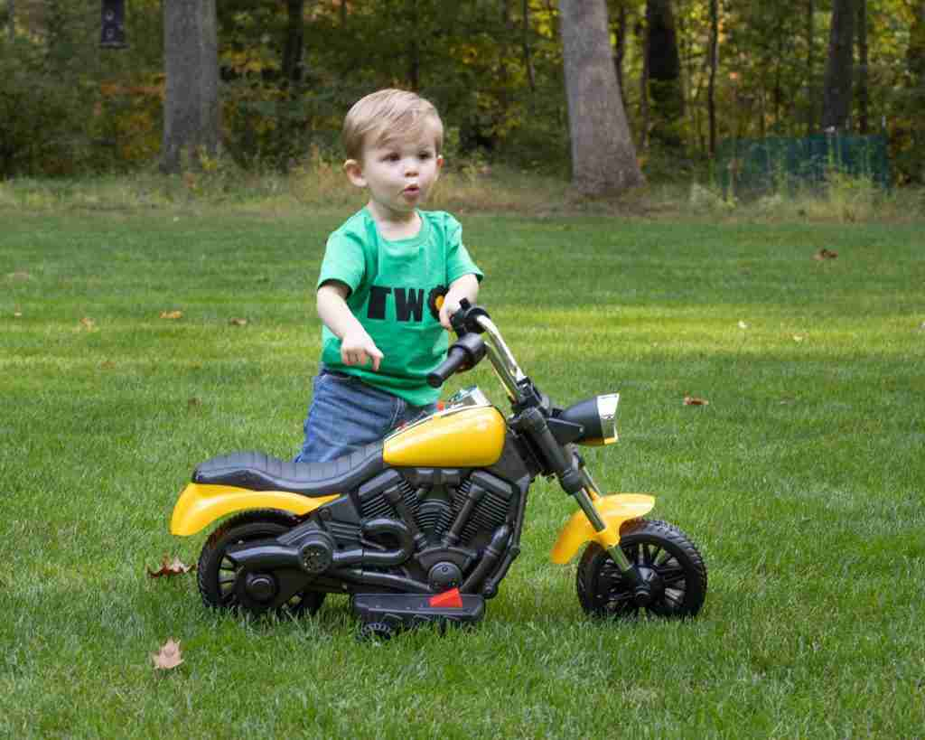 Toddler standing next to a toddler-sized motorcyle