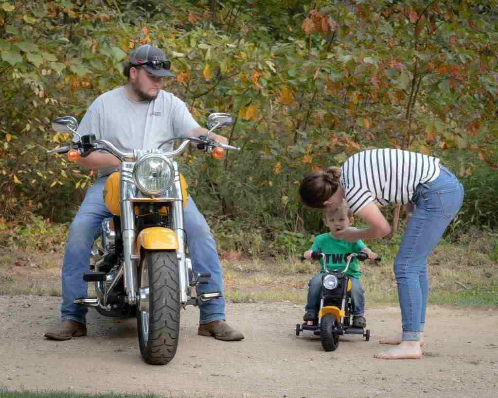 mom wiping off toddler's face while he sits astride a mini motorcycle next to dad on a full sized Harley
