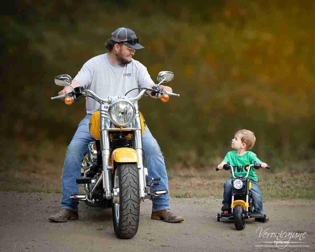 Dad and toddler son sit astride matching Harleys side-by-side