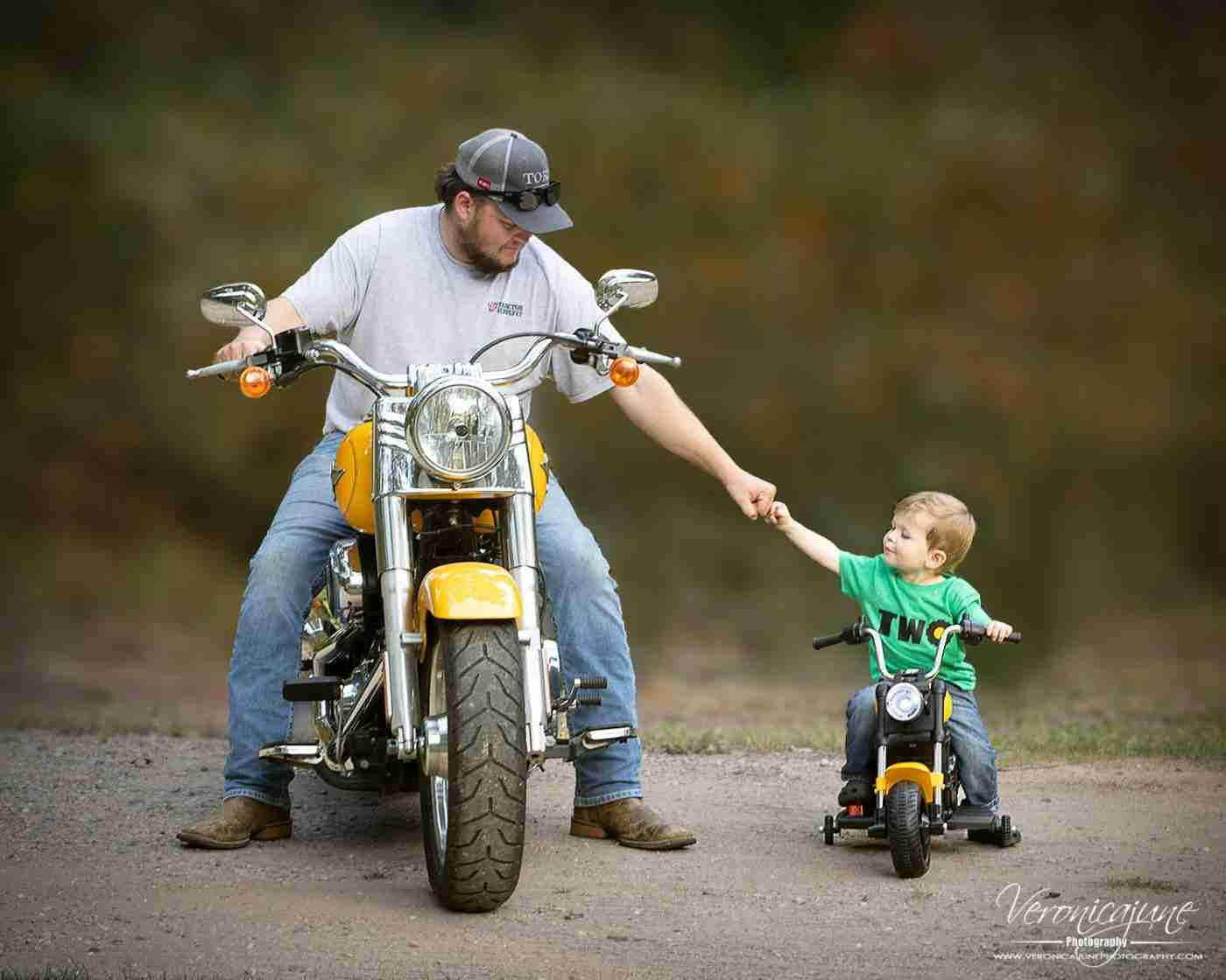 Dad and toddler son fist bump while sitting side by side on matching Harleys