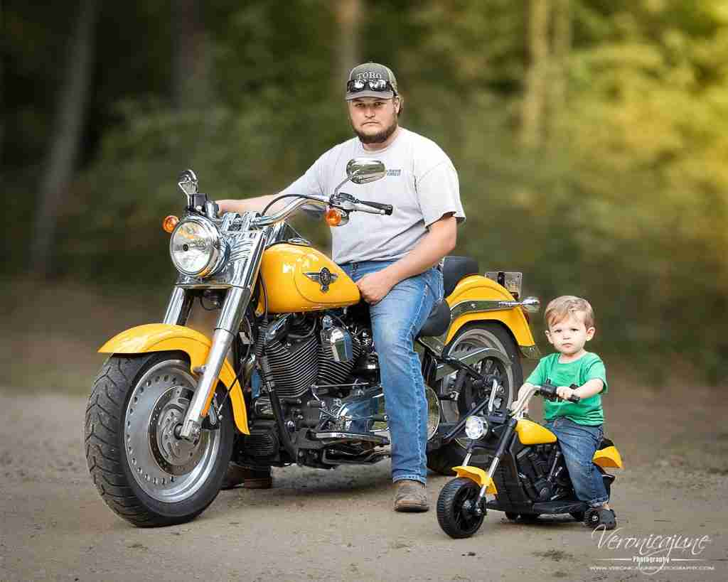 Dad and toddler son sitting side by side on matching Harleys