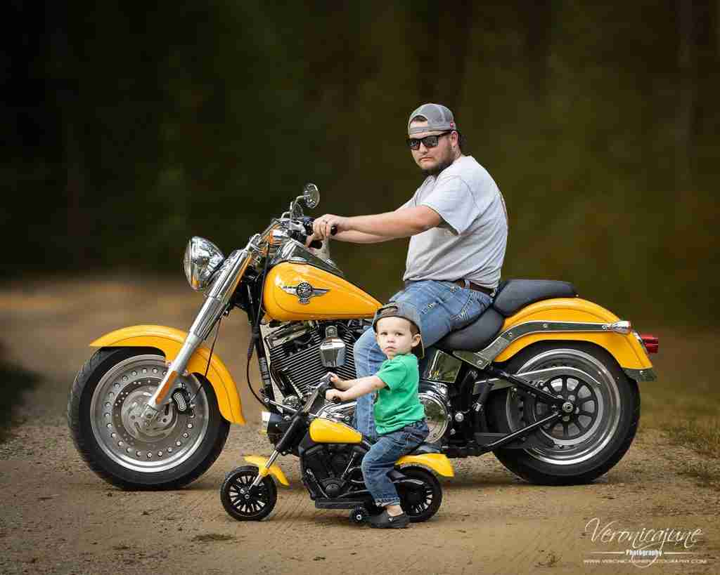 Father and toddler son side together on matching Harleys
