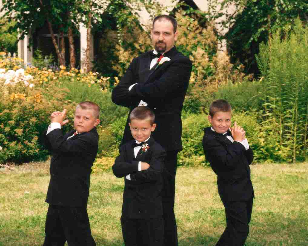 Dad and 3 boys posing as Charlie's Angels