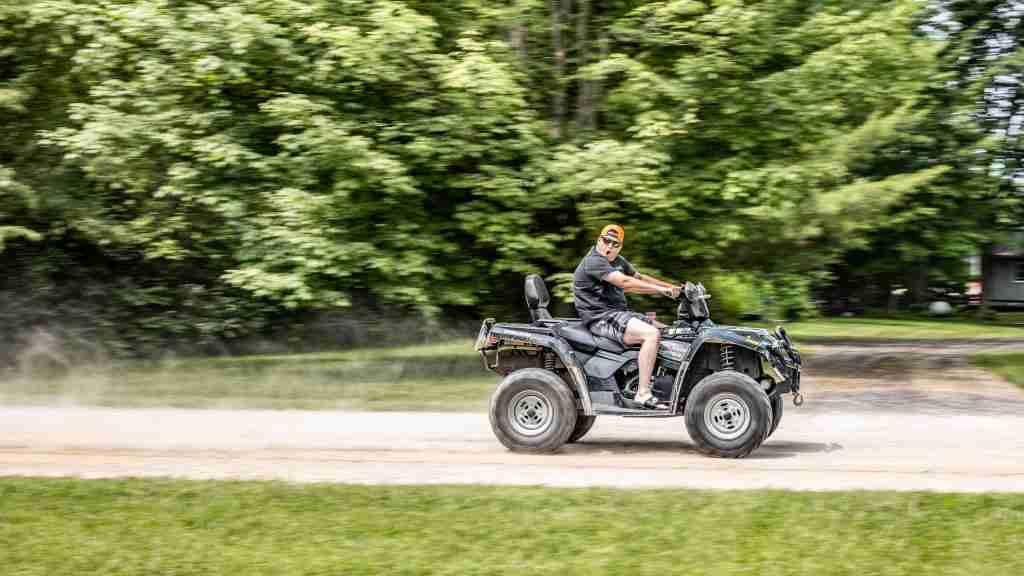 dude on a quad driving to the right making a cool face