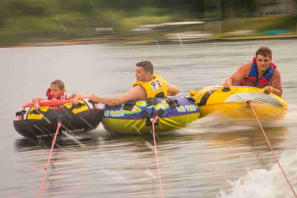 3 boys on water tubes with panning action