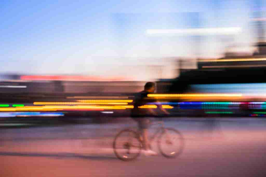 Panning shot with man on a bike and lights behind him