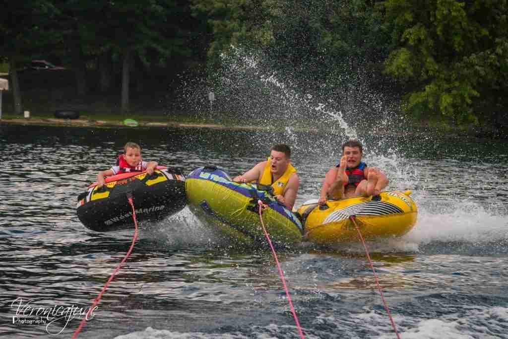 3 boys on water tubes with water splashing