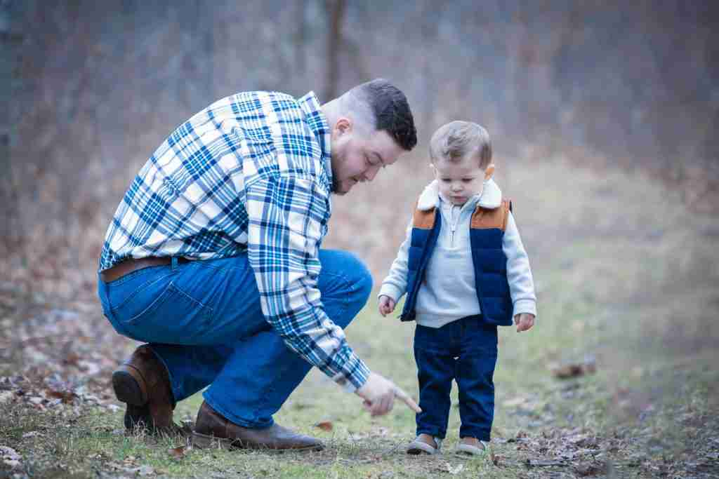 Father and son looking at something on the ground