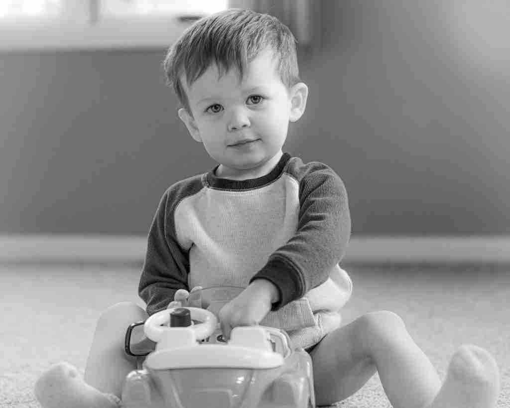 black and white photo of a toddler with a car