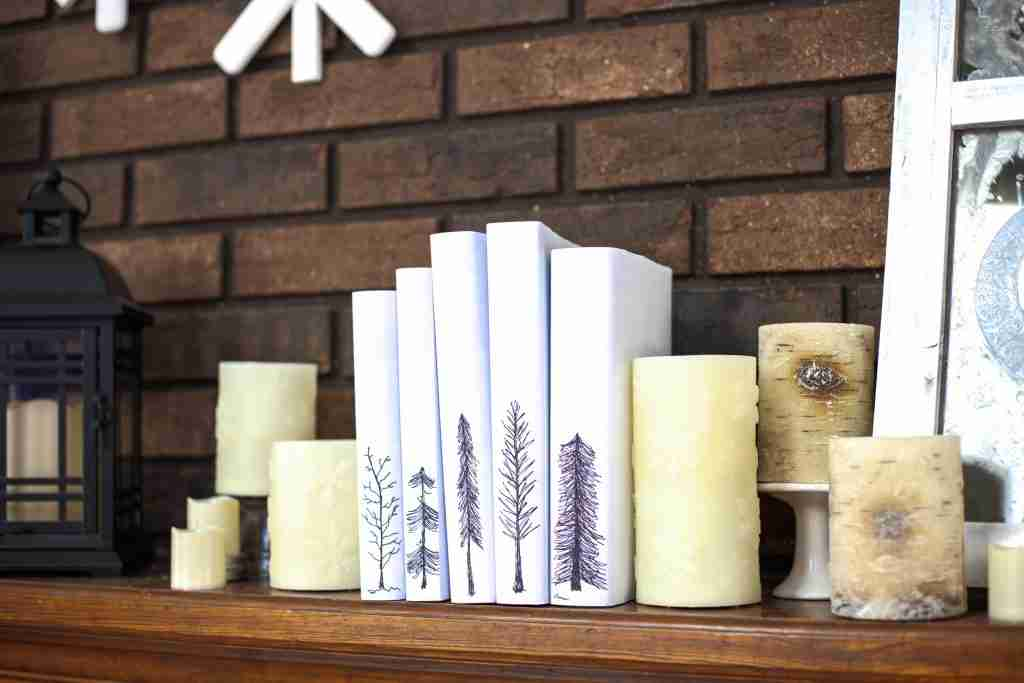 Winter books covered with white paper and cozy hand-penned trees
