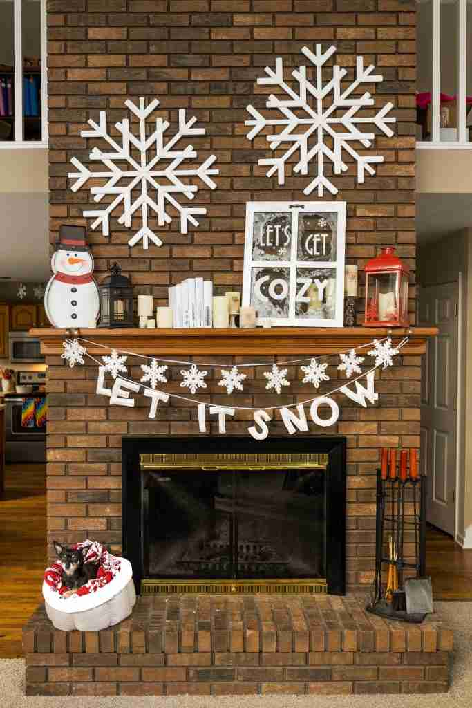 Cozy fireplace mantle with snowflakes and a frosted window