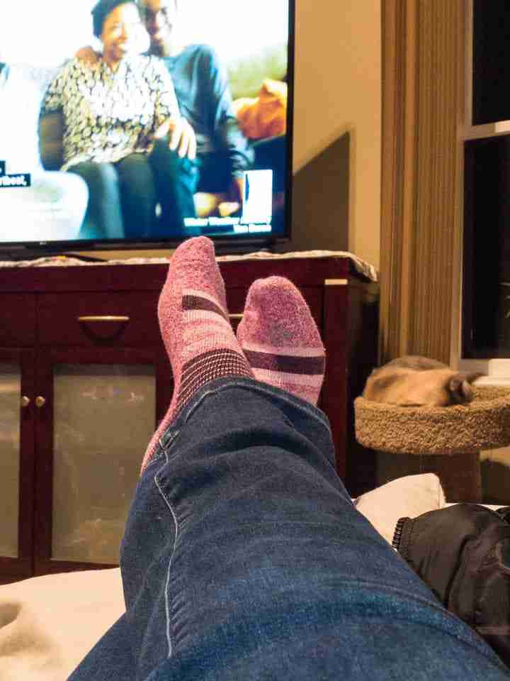 Pink socked feet with tv background