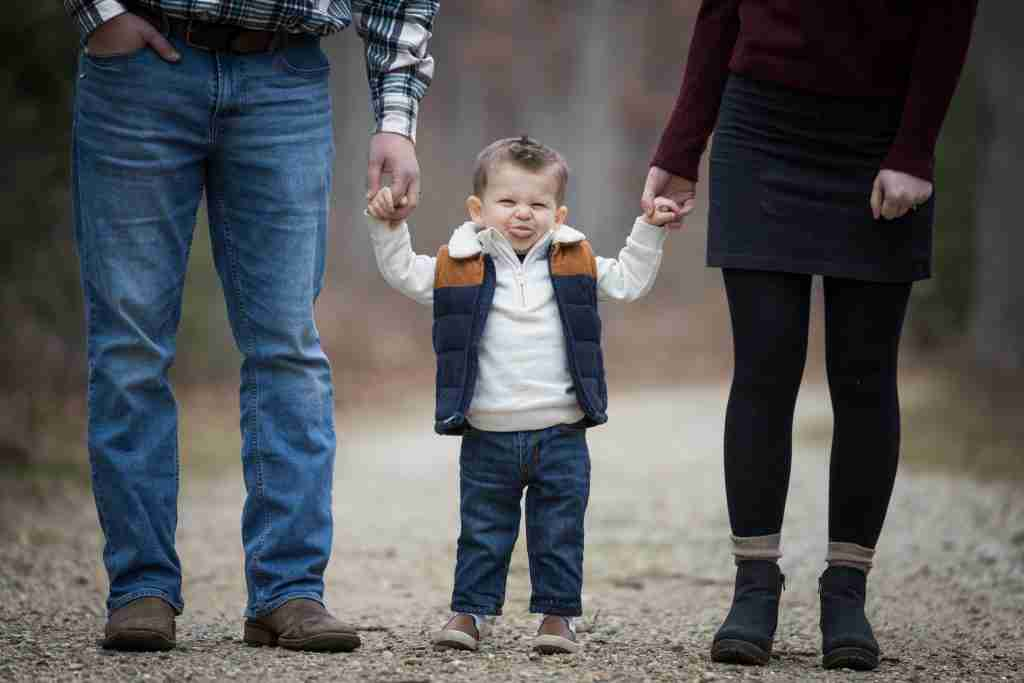 Little boy sticking tongue out flanked by parents holding hands
