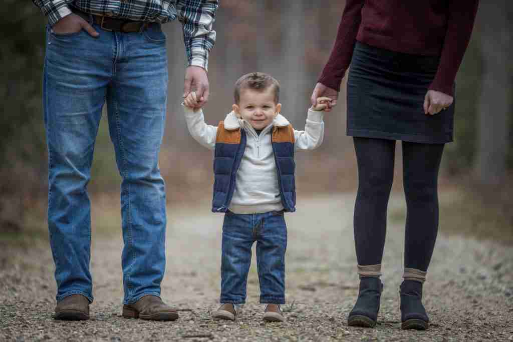little boy smiling sweetly flanked by parents holding hands