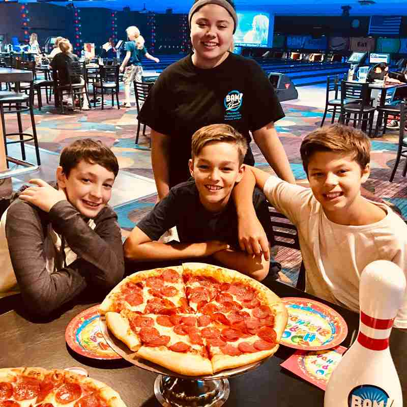 kids having a pizza and bowling birthday party in kid's party in Holland Michigan